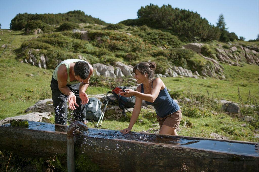 Zwei Wanderer spritzen mit Wasser an einer Tränke in den Bergen