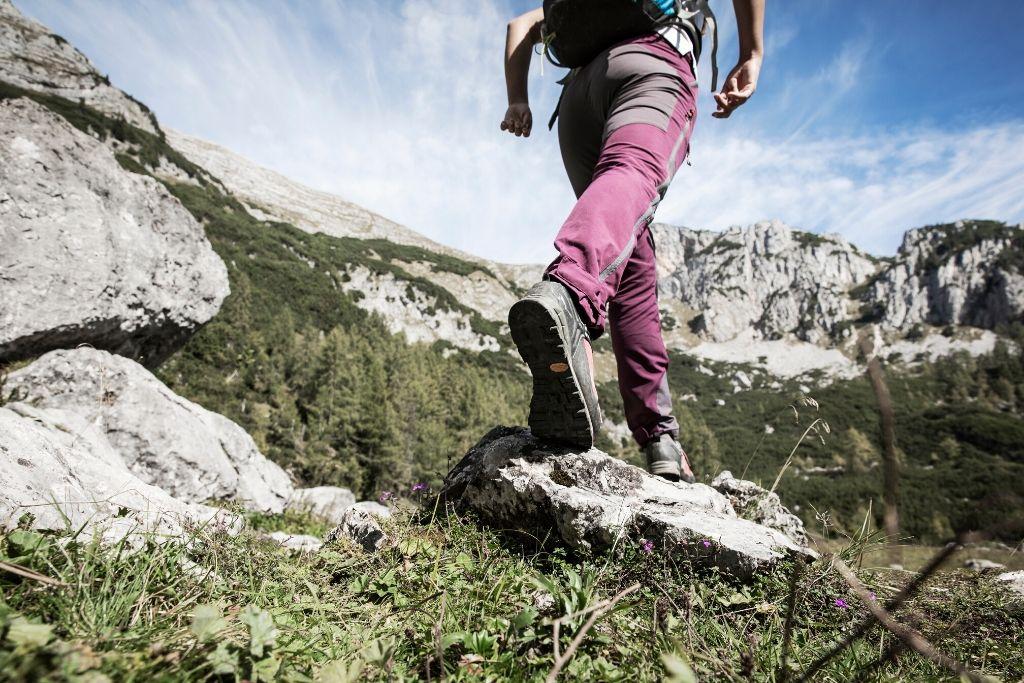 Wanderer läuft sicher über Felsen und Wiesen in den Bergen