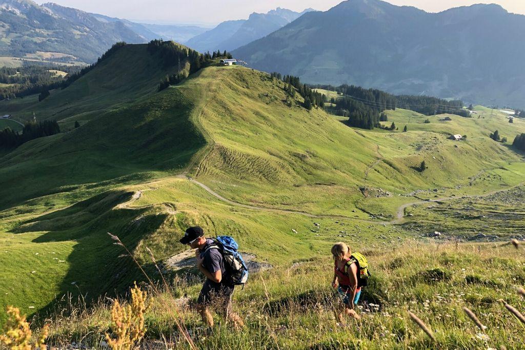 Wanderer auf kleinem Pfad einer Bergwiese mit toller Aussicht