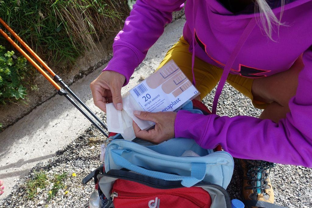 Wanderer holt Pflaster aus Notfallset im Rucksack