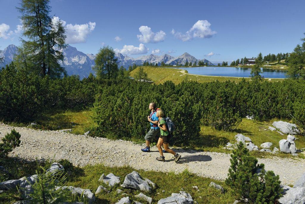 Zwei Wanderer laufen auf Schotterweg mit Bergpanorama und Alpensee im Hintergrund