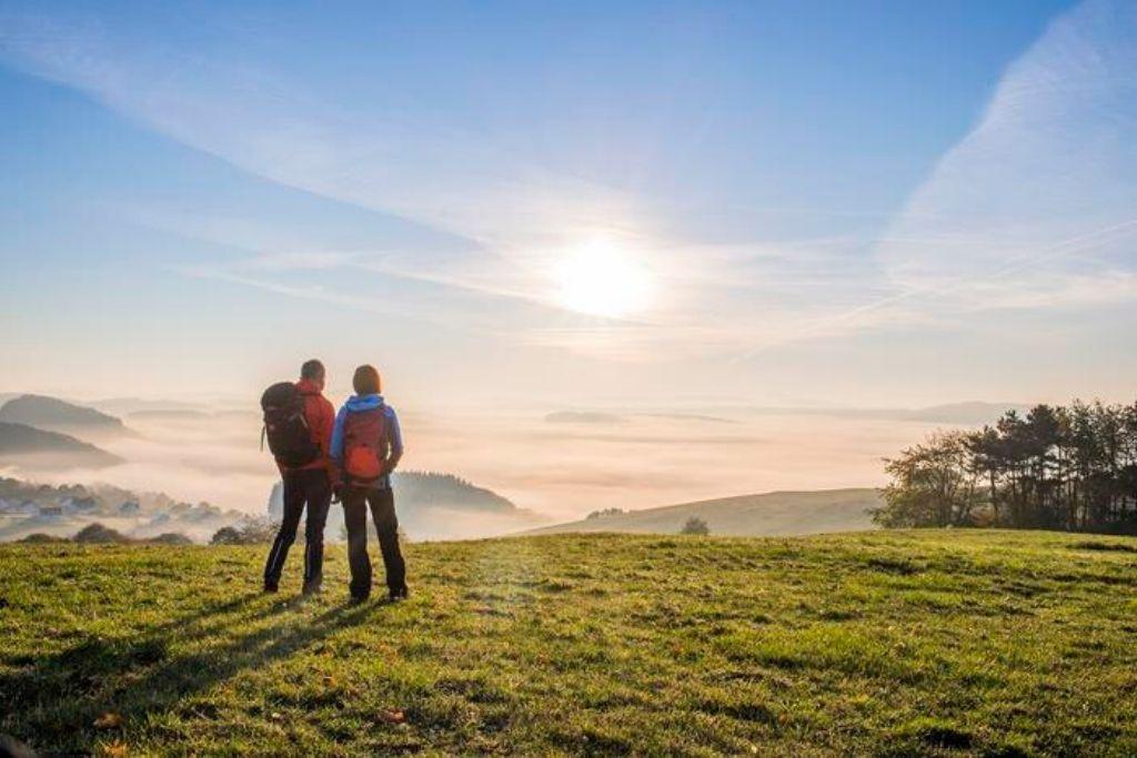 Wanderer beobachten den Sonnenaufgang auf der Hügelkuppe