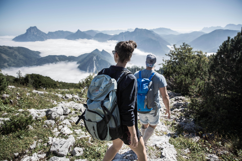Zwei Wanderer auf einer steinigen Bergkuppe schauen auf wolkenverhangene Berggipfel