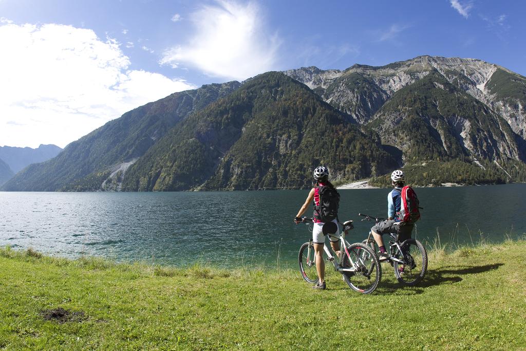 Zwei Radfahrer stehen am Ufer vom Achensee