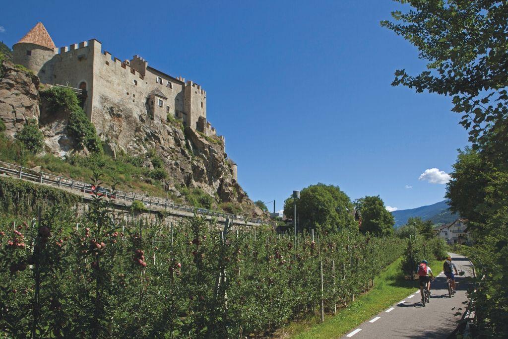 Zwei Radfahrer auf asphaltiertem Radweg unterhalb des Schlosses Kastelbell im Vinschgau
