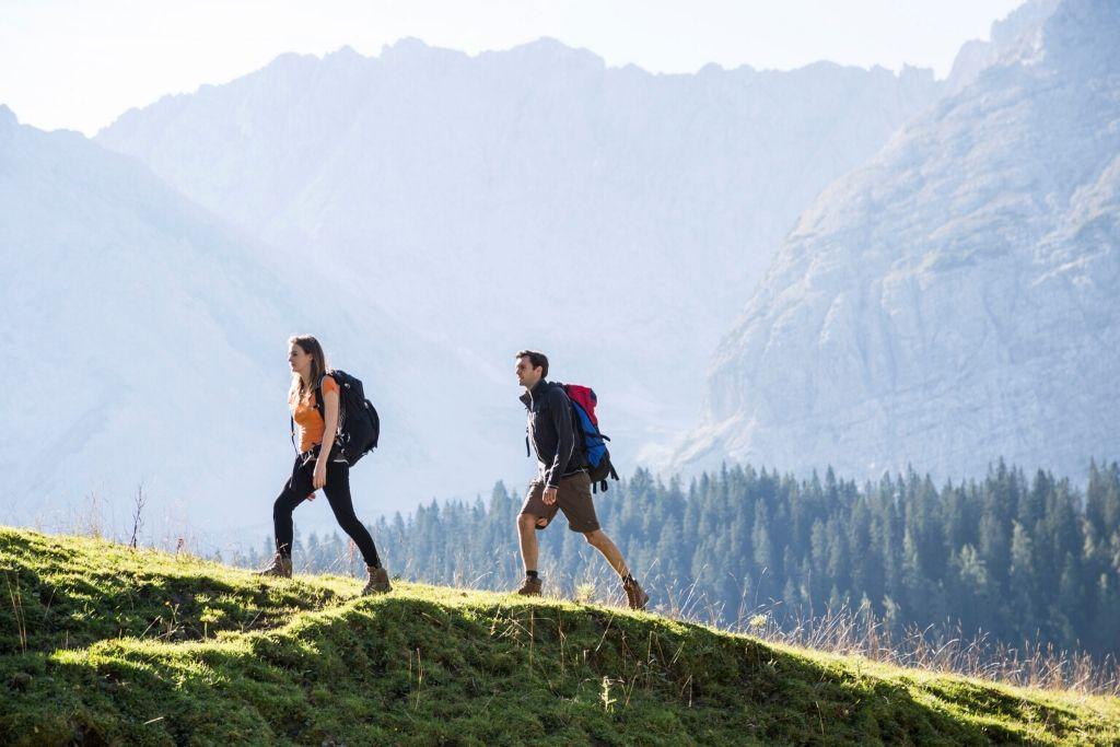Zwei Wanderer mit Rücksack laufen über einen Wiesenpfad. Im Hintergrund ragen die Berge in die Höhe.